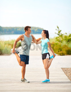smiling couple stretching legs on beach