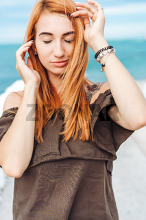 young woman with red hair posing at the camera