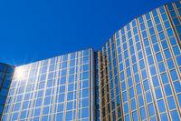 Modernes Bürogebäude mit Glasfassade vor blauem Himmel