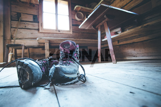 Alpine boots on rustic wood floor in an abandoned mountain chalet in Austria