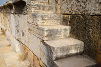 The steps of the amphitheater. Stone limestone and marble. Ancient antique amphitheater in city of Hierapolis in Turkey