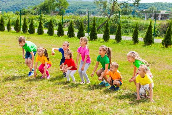 Cheerful group of kids have fun on the grass
