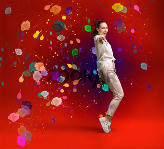 young and beautiful dancer posing in studio at colored background