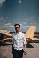 A man standing on the background of a small single engine plane.