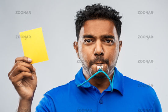 indian referee whistling and showing yellow card