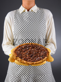 Closeup of a homemaker in an apron and oven mitts holding a fresh baked holiday Pecan Pie.