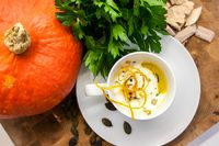 Pumpkin and carrot soup, with cream and parsley on dark wooden background.