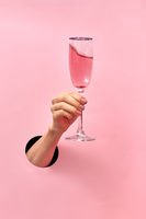 Rose wine glass in a female's hand from the hole in the wall.