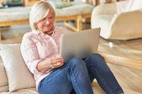 Seniorin auf der Couch am Laptop Computer