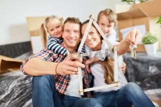 Familie mit Zollstock in Form von Haus