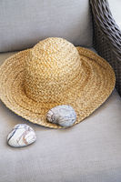 Straw hat with heart shaped rocks on chair