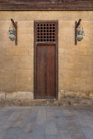 Wooden closed door and Arabic glass street lanterns hanged on a wooden pole in old stone bricks wall