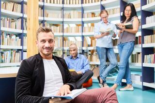 Mann beim Buch lesen gemeinsam mit jungen Leuten
