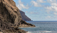 Picturesque landscape taken in Tenerife, Canary Islands, Spain. Rocky coastline black volcanic mountains cloudy sky and view to the calm Atlantic Ocean
