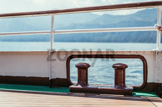 Boat tour: Boat railing, view over azure blue water and mountain range. Lago di Garda, Italy