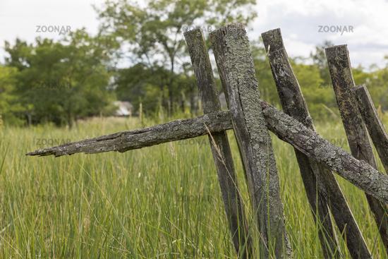 Verwitterter Holzzaun mit Gras überwachsen