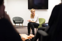 Instructor teaching first aid cardiopulmonary resuscitation course and use of automated external defibrillator on CPR workshop.