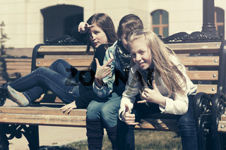 Group of happy teen girls sitting on bench in city street