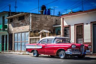 Amerikanischer roter Oldtimer parkt in der Seitenstrasse in Santiago de Cuba - Serie Kuba Reportage