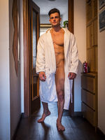 Sexy man in bathrobe standing in apartment corridor