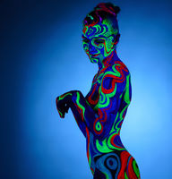 Nude girl posing with glowing patterns on her body