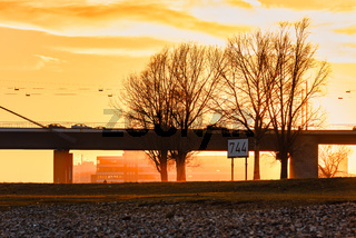 DUESSELDORF, GERMANY - JANUARY 20, 2017: The winter sun goes down over a large bridge and bathes everything in orange warm light