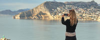 Rear view woman holding smartphone take photography of mountains hillside Calpe townscape and Mediterranean Sea. Capture moment, enjoy view tourist travelling visiting new places concept. Calpe, Spain