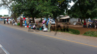 local people wait at the bus stop and chat after coming from the daily market in the town center of Moshi