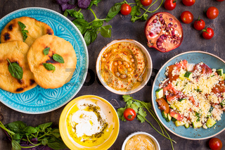 Table served with middle eastern vegetarian dishes. Hummus, tahini, pitta, couscous salad and buttermilk dip with olive oil