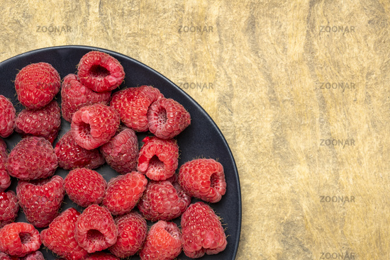 fresh red raspberries on black plate