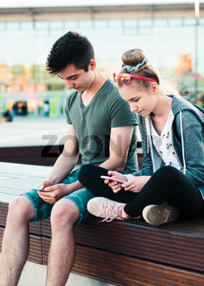 Couple of friends, teenage girl and boy,  having fun together with smartphones