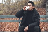 Young man sitted in a bench holding disposable coffee cup in the park in autumn season.