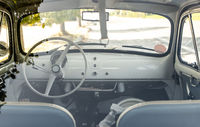 Interior of small white vintage car on the street. No people. White steering wheel.
