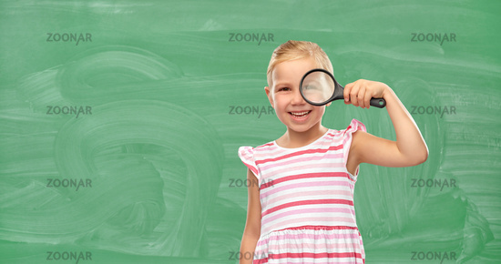 girl looking through magnifying glass at school