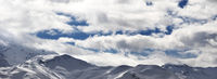 View on snowy mountains and sunlight cloudy sky in evening