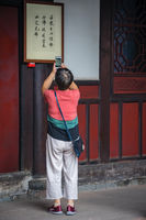 Woman taking pictures of chinese characters