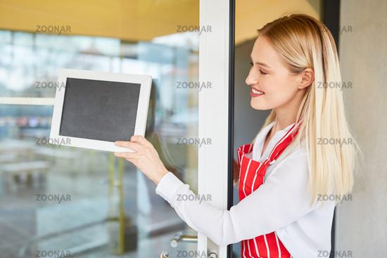 Kellnerin hängt leere Tafel an Restaurant