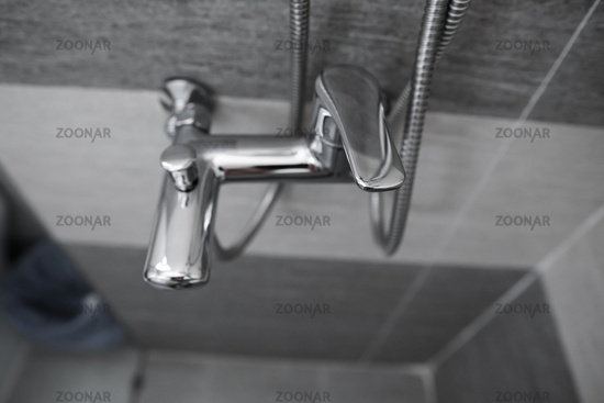 Modern designer tap and shower in bathroom. Closeup of chrome shower, faucet, in the bathroom covered decorative ceramic. Mixer cold hot water.
