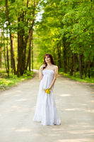beautiful girl with dandelion flowers on forest road