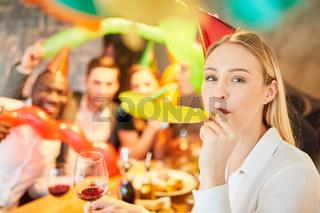 Frau auf einer Party im Karneval pustet in eine Tröte