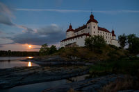 Long exposure of Lacko castle in the evening with full moon rising over lake Vanern, Lidköping, Sweden
