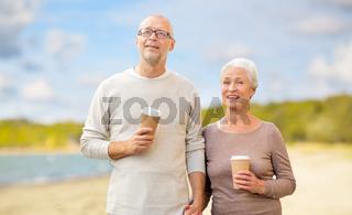 senior couple with takeaway coffee on beach