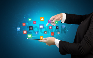 Hand holding tablet and application icons above
