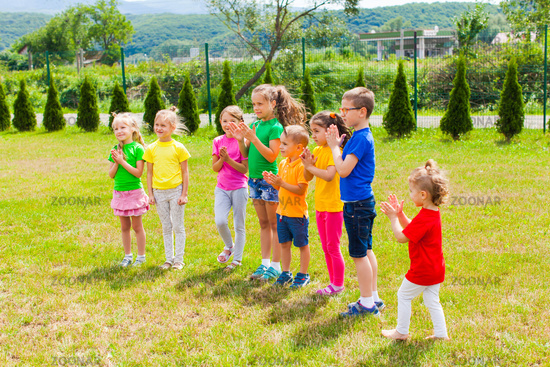 Group of kids clapping hands on the green grass