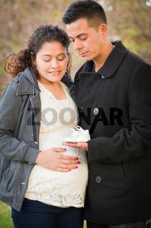 Hispanic Pregnant Couple Holding Baby Shoes