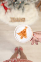 Female holding cappuccino with Christmas tree design on froth