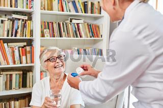Altenpflegerin gibt einer Seniorin ihr Medikament