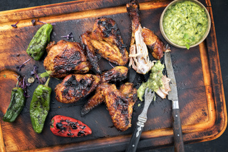 Traditional Caribbean barbecue jerk chicken wings and drumsticks with chimichurri sauce