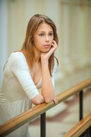 Young beautiful woman with long hair near wooden railing.
