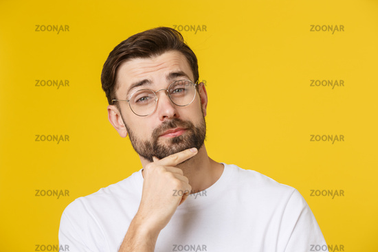 Thinking man isolated on yellow background. Closeup portrait of a casual young pensive man looking up at copyspace. Caucasian male model.